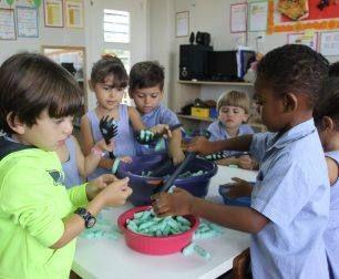 Students do sensory activity using colored pasta